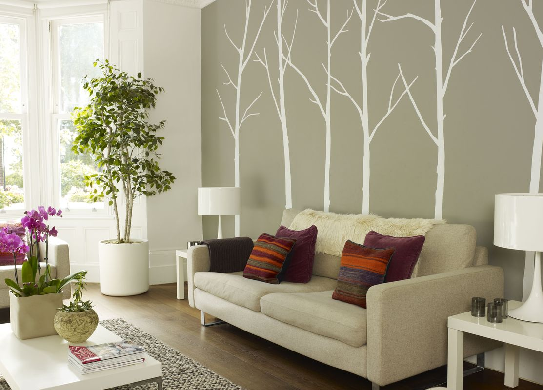 Srriped cushions on cream sofa with tree wall deco in living room of London home, UK